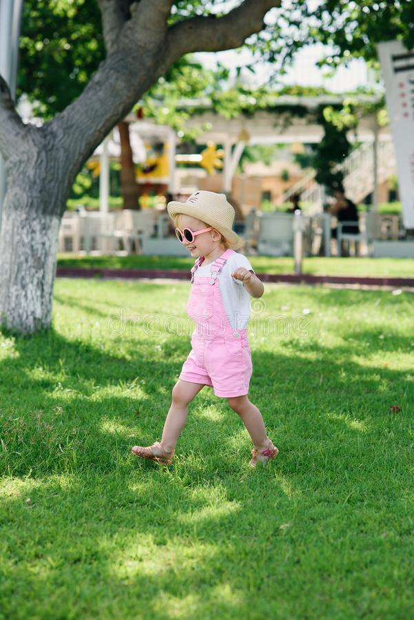 Стильная девушка в розовые прозодежды, шляпа и розовые прогулки стекел на зеленой траве o стоковое изображение rf