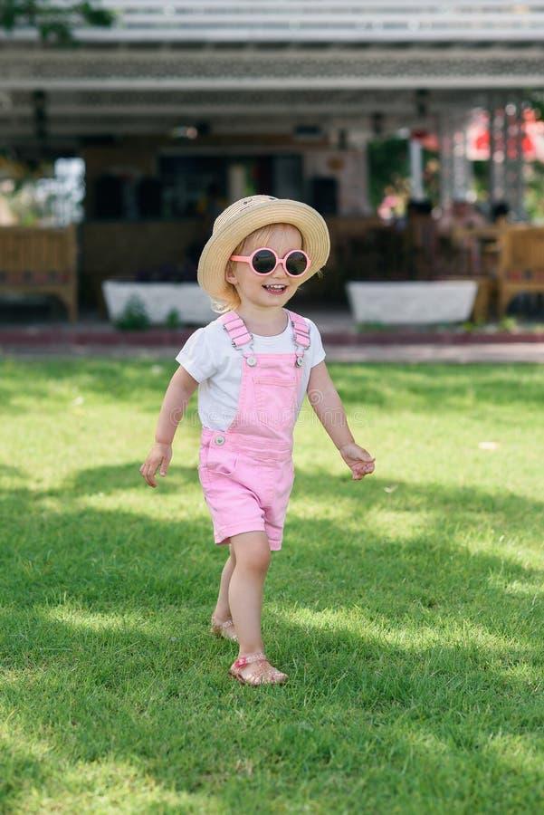 Стильная девушка в розовые прозодежды, шляпа и розовые прогулки стекел на зеленой траве o стоковые изображения rf