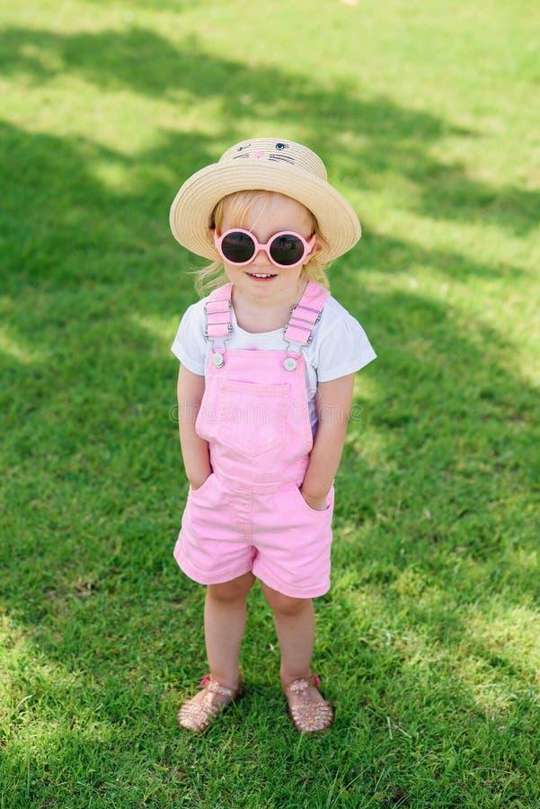 Стильная девушка в розовые прозодежды, шляпа и розовые прогулки стекел на зеленой траве o стоковые фото