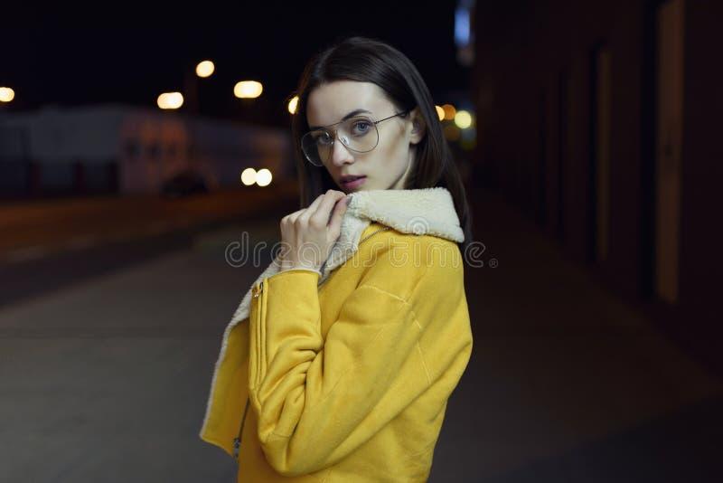 Стильная девушка представляя в желтой куртке и стеклах, освещенных светами центра города к ночь Мода Womenswear нот bokeh предпос стоковые изображения