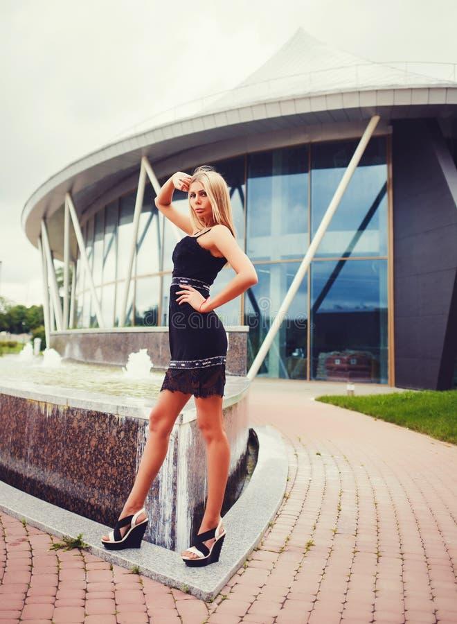 Стильная девушка при длинные ноги представляя на городе лета стоковое изображение