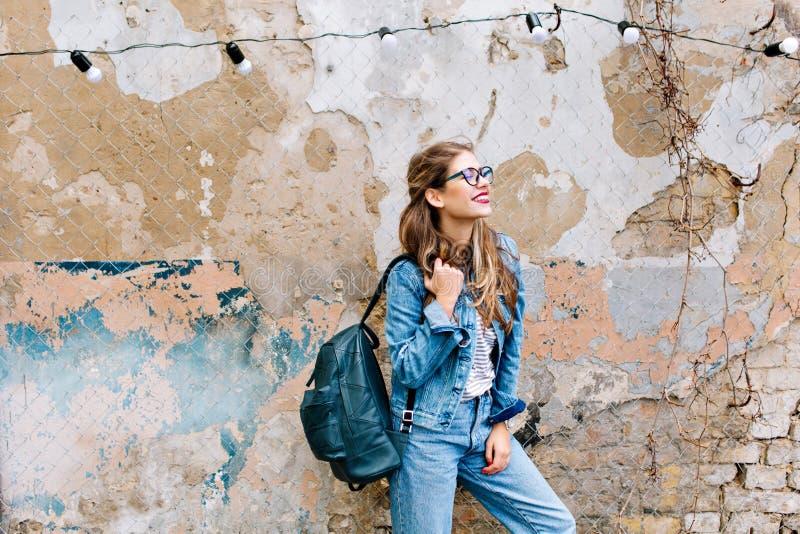 Стильная девушка хипстера в ретро костюме джинсов представляя перед старой кирпичной стеной Ультрамодная молодая женщина с положе стоковая фотография rf