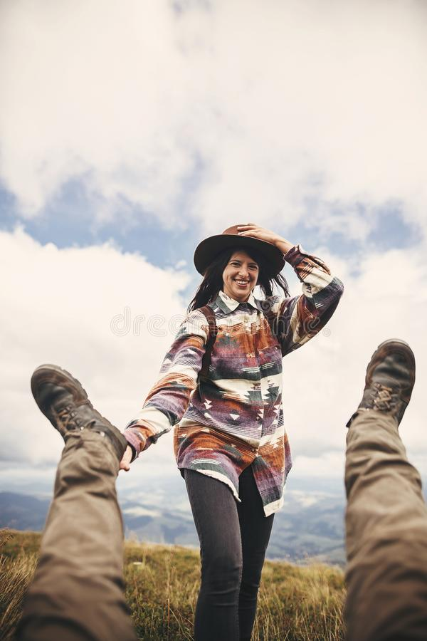Стильная девушка хипстера в шляпе держа ноги падая человека, смешной момент поверх гор Счастливая молодая женщина имея потеху и стоковая фотография rf