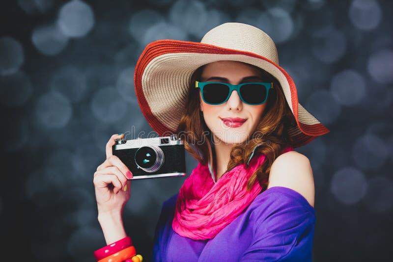 Стильная девушка redhead в шляпе и солнечных очках с камерой стоковая фотография rf