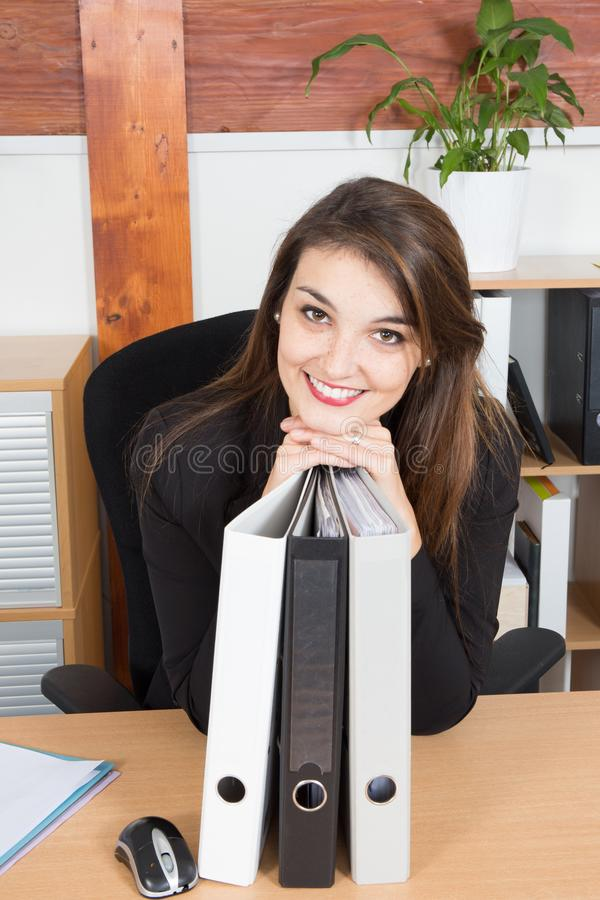 стильная довольно молодая склонность коммерсантки на папке на ее столе в усмехаться офиса стоковое фото rf