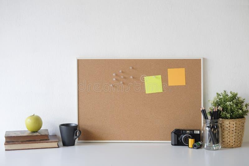 Стильная доска таблицы и вывесить кружку его, книги, карандаша, камеры и кофе на таблице со стеной стоковые фото