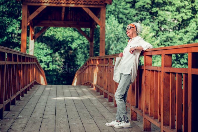 Стильная достигшая возраста дама полагаясь на коричневом деревянном мосте стоковые изображения rf