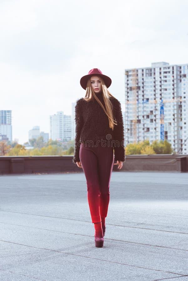 Стильная женщина в бургундской шляпе и осень оборудуют идти на a стоковая фотография rf