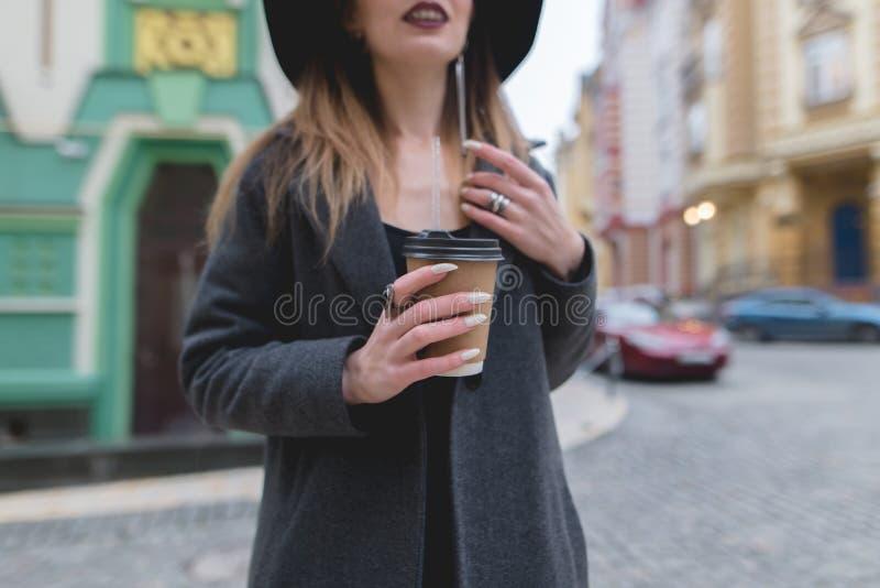 Стильная женщина держит чашку кофе или чай в ее руках Горячее питье в руках красивой женщины стоковые изображения rf