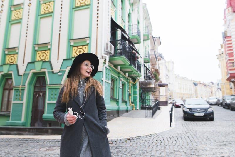 Стильная женщина идя вдоль улиц красивого города и слушая к музыке в наушниках стоковое изображение rf