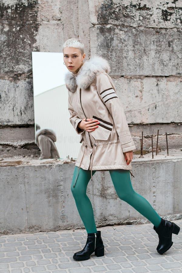 Стильная и красивая девушка с короткими волосами на улице около бетонной стены стоковые изображения