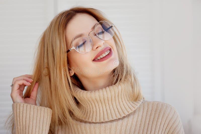 Стильная и красивая молодая блондинка в бежевом сверхразмерном свитере Молодая женщина с стеклами стоковое фото