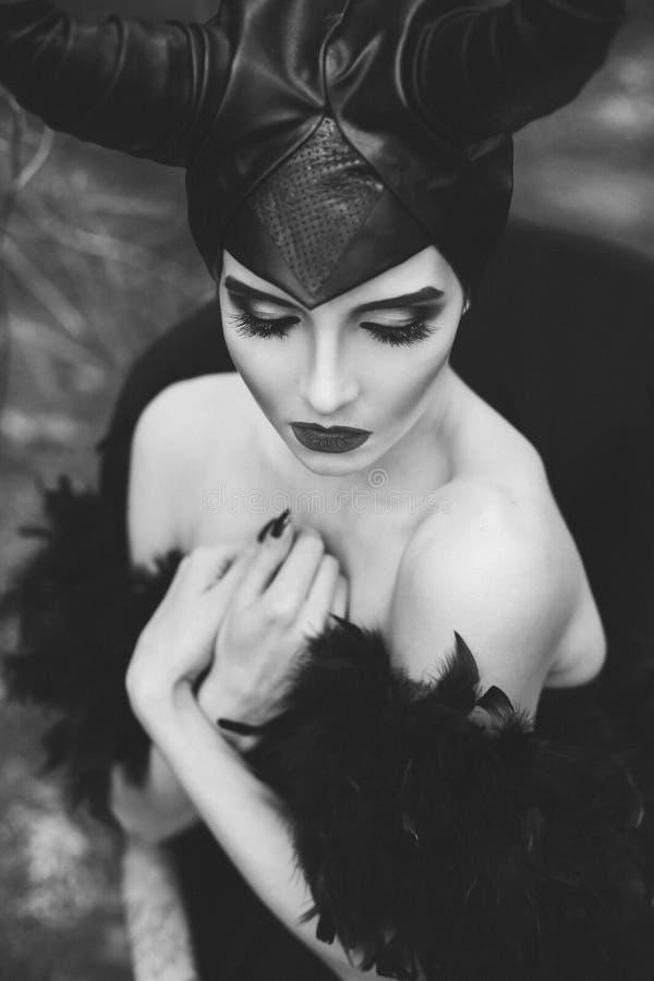 Стильная и модная девушка модели брюнет в изображении Maleficent представлять среди мистического леса - рассказ сказки стоковые фото