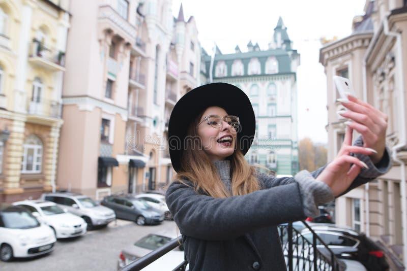 Стильная и положительная девушка усмехается и принимается selfie на предпосылке красивого старого городка стоковая фотография rf