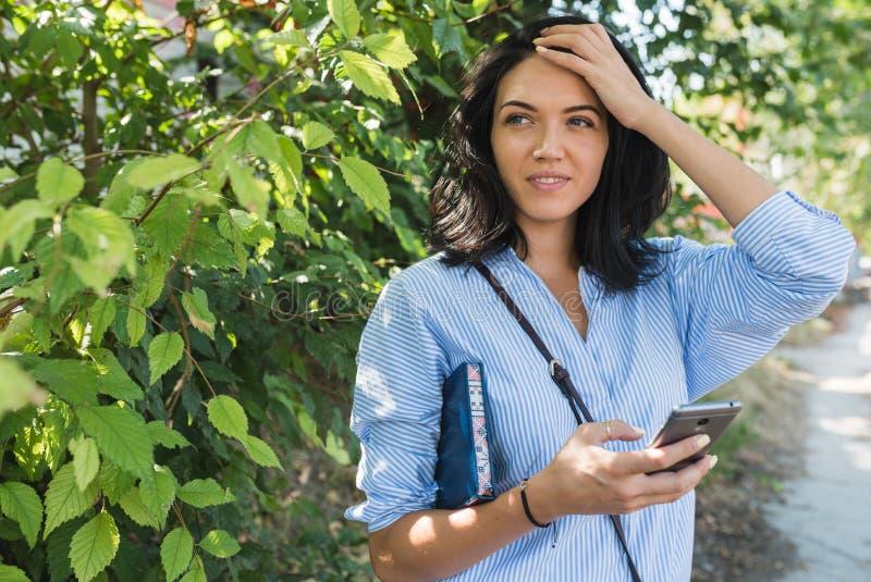 Стильная кавказская женщина используя онлайн сообщение со свободным беспроводным connectionon интернета ее сет-позволенный умный  стоковое изображение rf