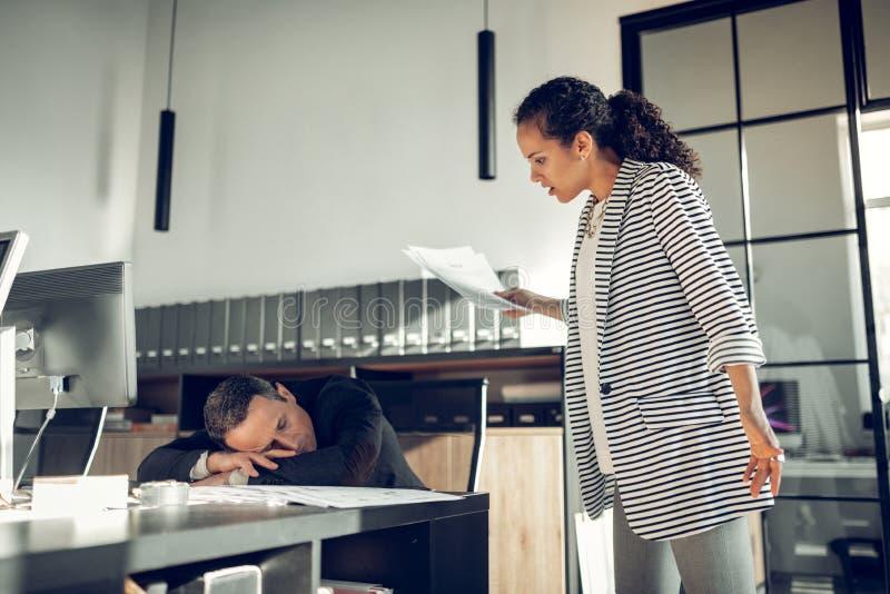 Стильная коммерсантка смотря ее спать ассистента стоковые фотографии rf