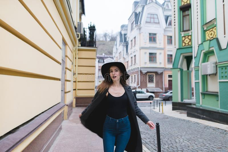 Стильная красивая женщина представляет к камере на фоне красивой старой улицы городка стоковое изображение