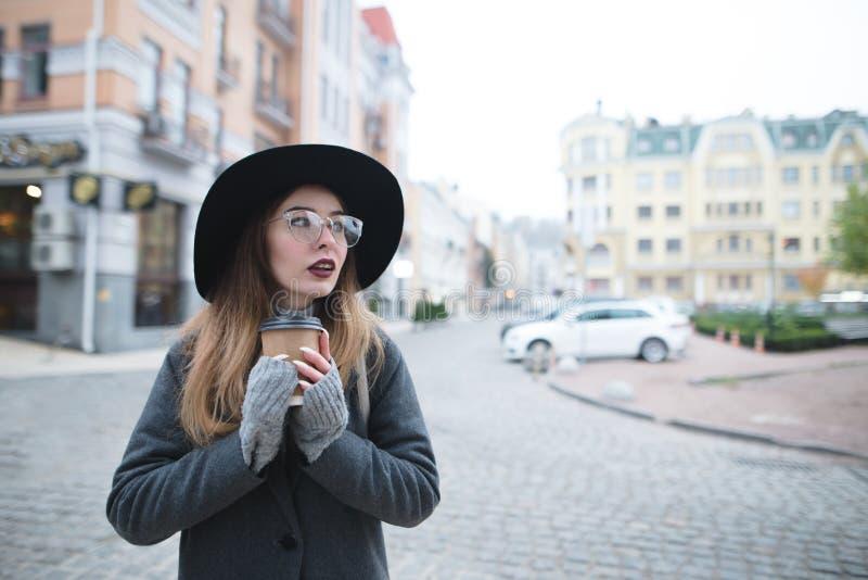Стильная красивая женщина с кофе в ее стойках рук на заднем плане ландшафта старого города стоковое изображение rf