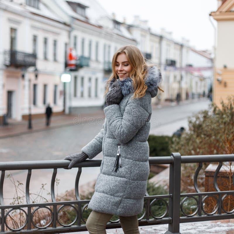 Стильная красивая молодая женщина в outerwear теплой зимы модном стоит на улице около загородки утюга черной стоковая фотография