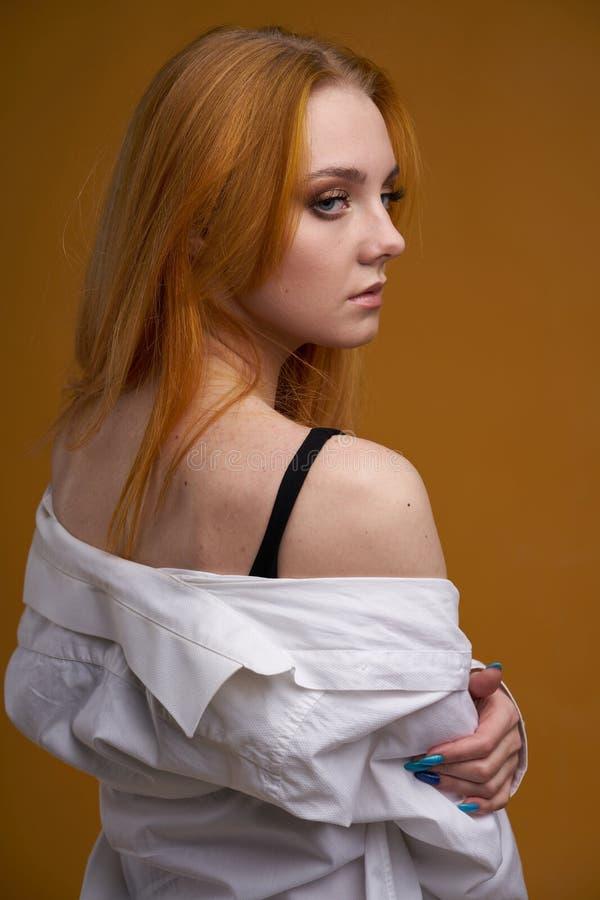 Стильная маленькая девочка с вьющиеся волосы, усмехающся cutely, представляя, на желтой предпосылке стоковое фото