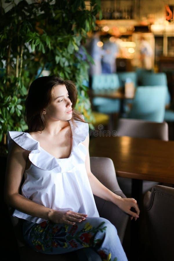 Стильная милая коммерсантка сидя на кафе и нося белой блузке с этническими джинсами стоковые изображения rf