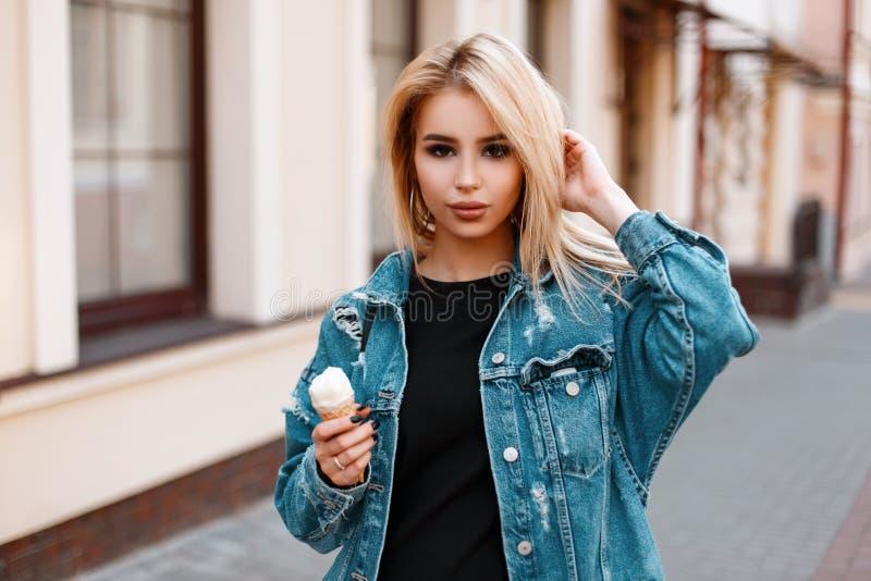 Стильная милая красивая молодая женщина в модном платье джинсовой ткани лета со сладкими прогулками мороженого вокруг города стоковые изображения rf