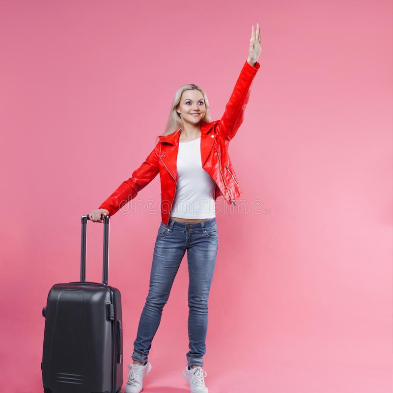 Стильная молодая белокурая девушка на розовой предпосылке Идущ к авиапорту, с сумкой перемещения таксомотор звонока стоковая фотография