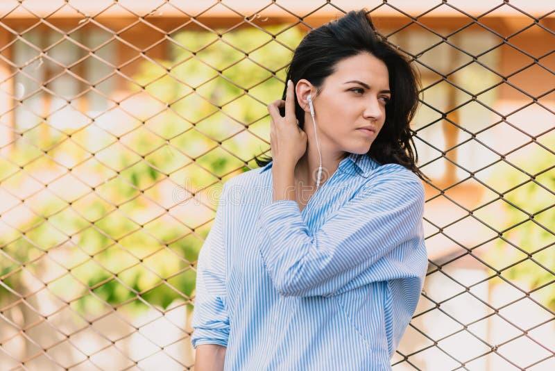 Стильная молодая европейская женщина, слушает музыку в наушниках, наслаждается приятными мелодиями, имеет хорошее настроение Люди стоковое изображение rf
