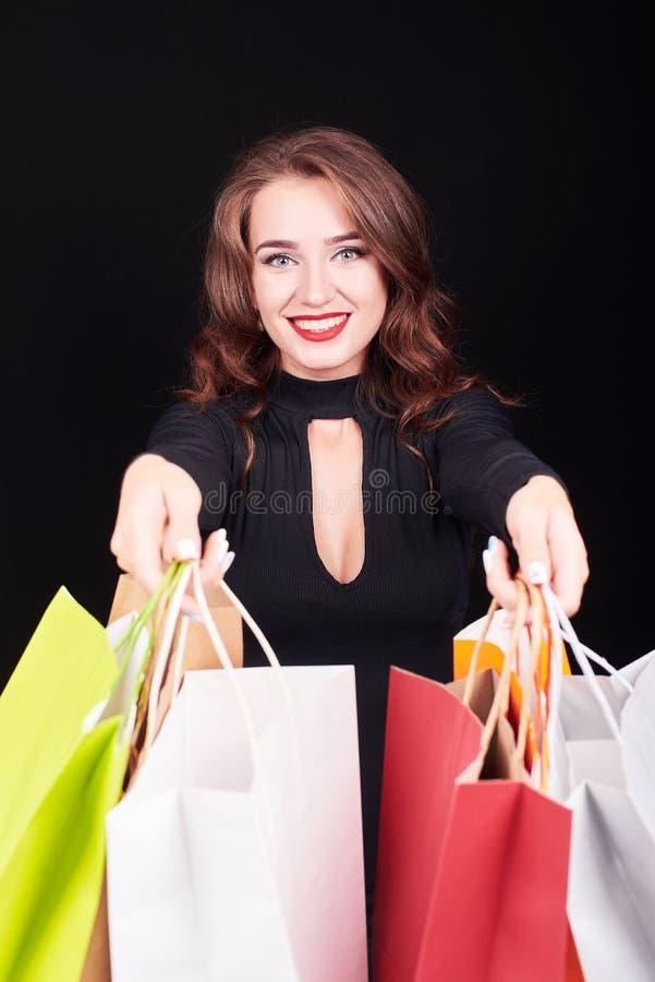 Стильная молодая женщина брюнета держа красочные хозяйственные сумки стоковые изображения rf