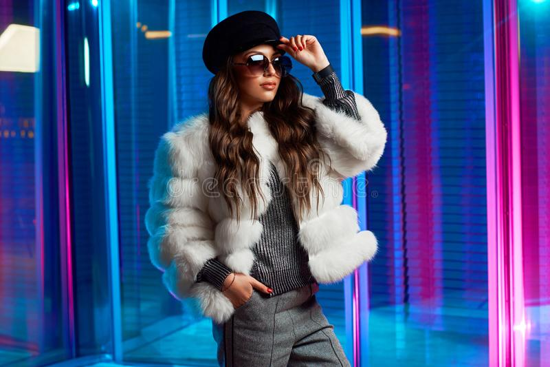Стильная молодая женщина в белой меховой шыбе и круглых солнечных очках стоковое изображение
