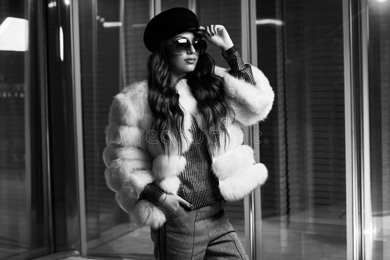 Стильная молодая женщина в белой меховой шыбе и круглых солнечных очках стоковое изображение rf