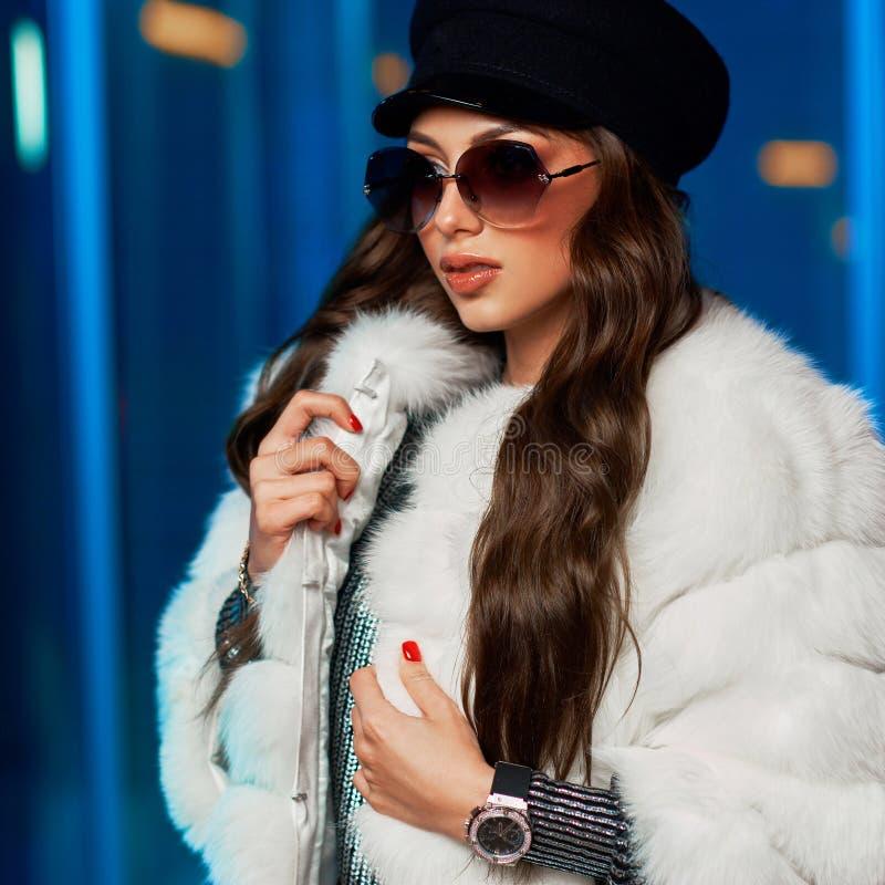 Стильная молодая женщина в белой меховой шыбе и круглых солнечных очках стоковая фотография