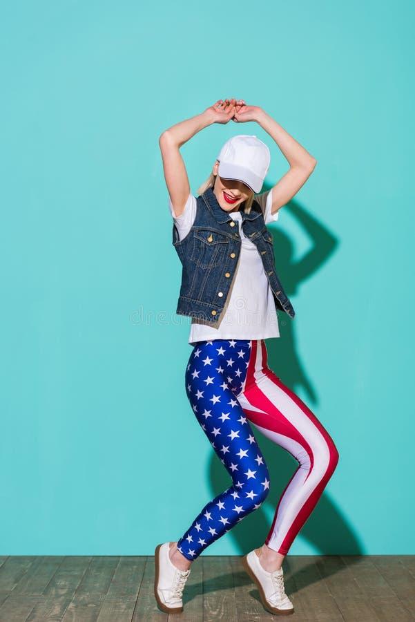 стильная молодая женщина в куртке и гетры джинсовой ткани рубашки крышки белых с представлять картины американского флага стоковая фотография