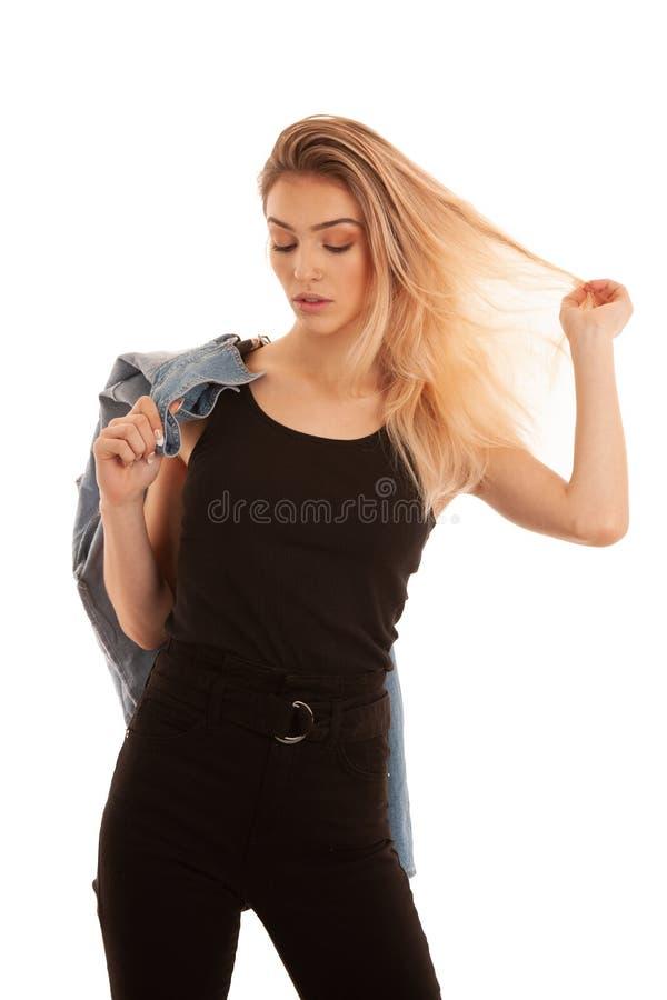 Стильная молодая женщина в черной стойке изолированной над белыми предпосылкой и улыбкой стоковая фотография rf