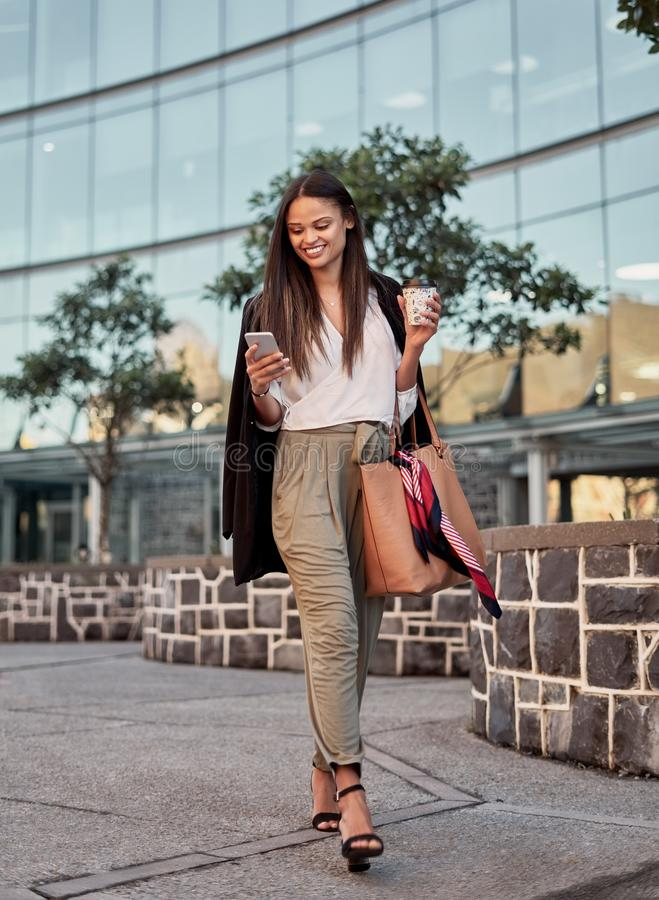 Стильная молодая женщина используя ее телефон пока идущ на улицу города стоковая фотография rf
