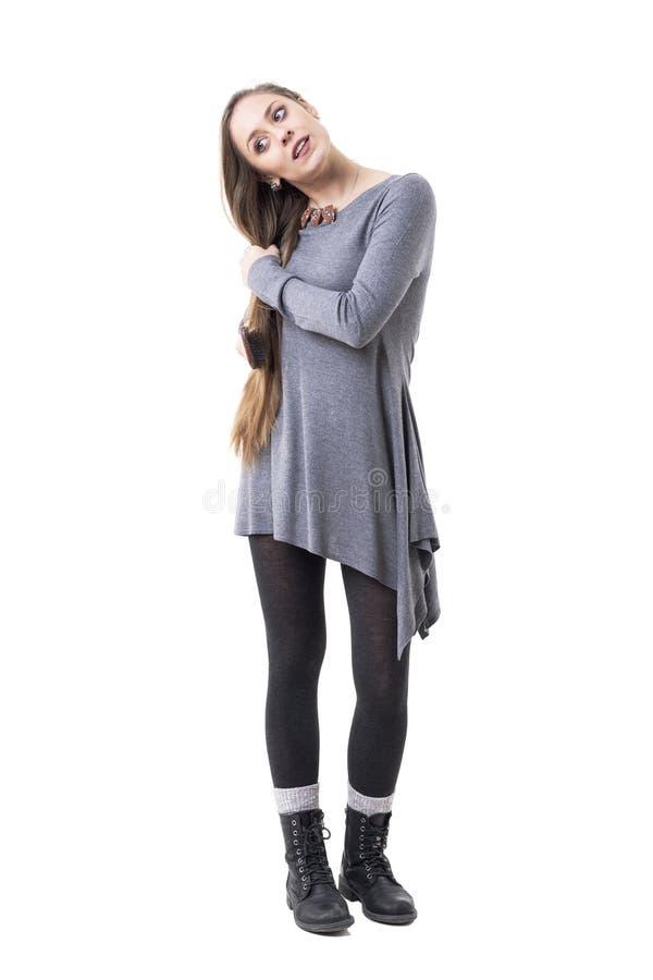 Стильная молодая тысячелетняя девушка смотря вниз пока чистящ ее длинные светлые волосы щеткой с щеткой для волос стоковое изображение rf