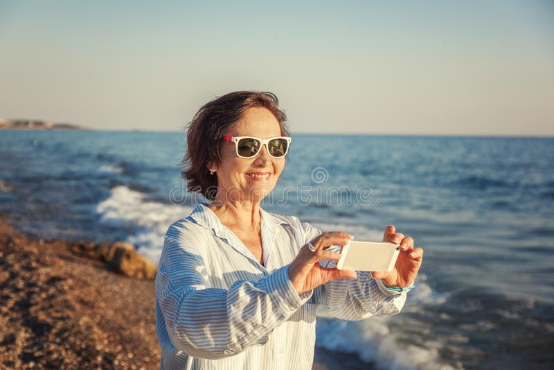 Стильная привлекательная зрелая женщина 50-60 делает фото передвижного pho стоковая фотография rf
