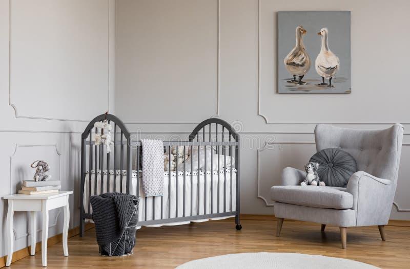 Стильная серая комната младенца с деревянной шпаргалкой, удобным креслом и белой таблицей с книгами, реальным фото с космосом экз стоковое изображение