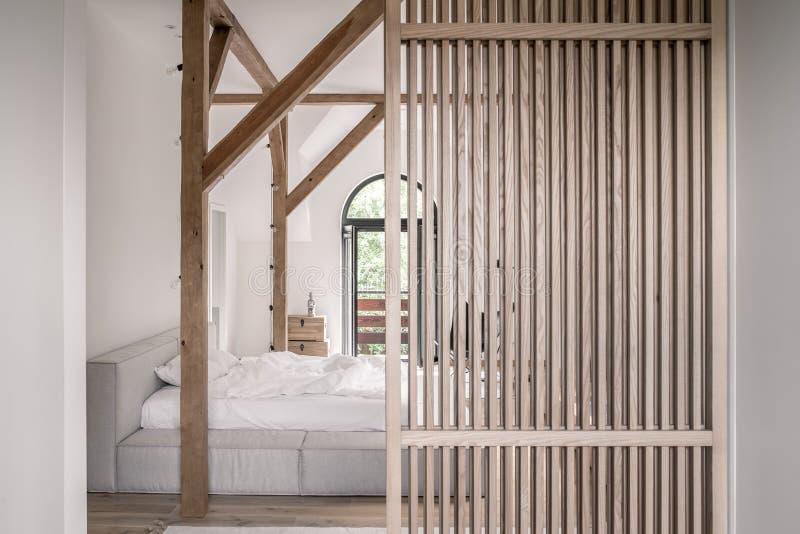 Стильная спальня в современном стиле с деревянными балками стоковое изображение rf