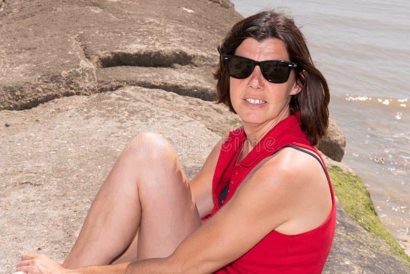 Стильная средняя достигшая возраста женщина в солнечных очках усмехаясь летом побережья стороны моря стоковые фотографии rf