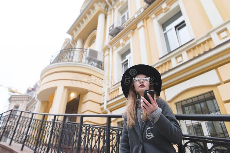 Стильная тазобедренная девушка наслаждается телефоном в улице под красивой старой архитектурой стоковые фотографии rf
