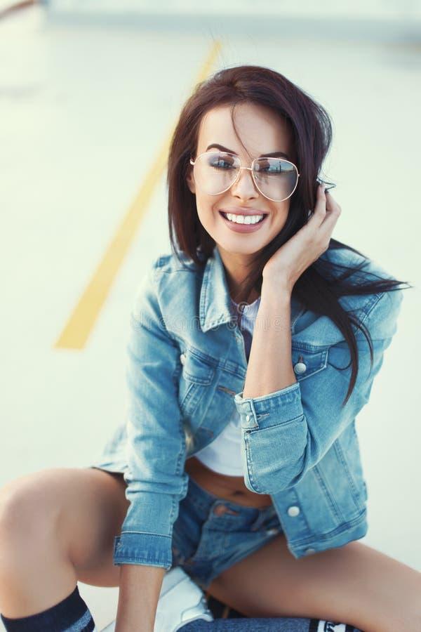 Стильная умная женщина брюнет в усмехаться джинсов внешний, городской fas стоковые фотографии rf