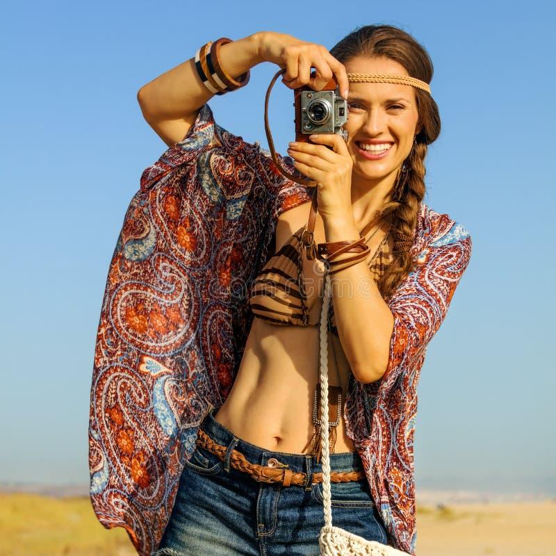 Стильная цыганская девушка стиля принимая фото с ретро камерой фото стоковая фотография