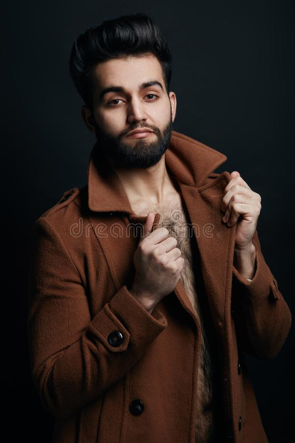 Стильное мачо касаясь воротнику его пальто и представляя к камере стоковая фотография rf
