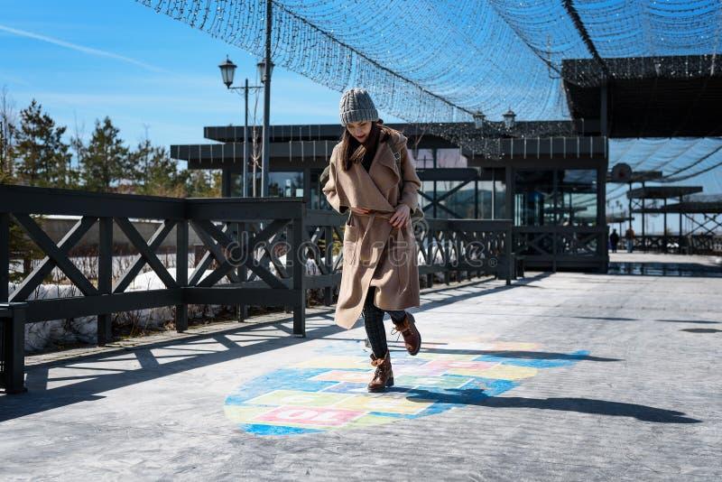 Стильно одетая средн-постаретая женщина играя классики, имея потеху как ребенок, скача и усмехаясь в свежем воздухе стоковые изображения rf
