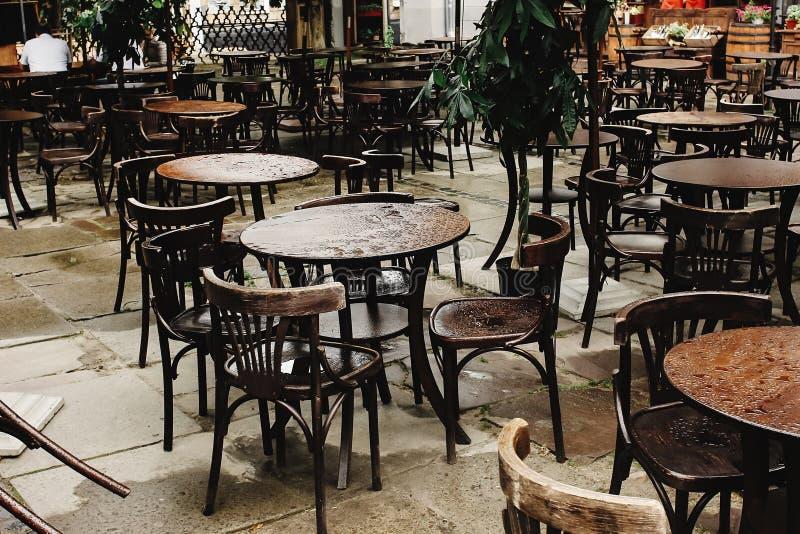 Стильные деревянные стулья и таблицы опорожняют на дождливом дне на улицах o стоковые фотографии rf