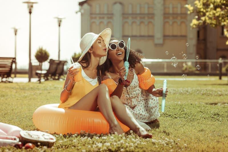 Стильные накаляя испуская лучи девушки дуя пузыри outdoors стоковые фотографии rf