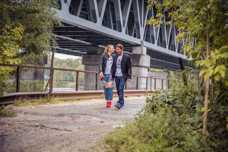 Стильные пары битника женщина boho цыганская нежно обнимая руку уверенно человека под покинутым мостом атмосферический чувственны стоковое фото