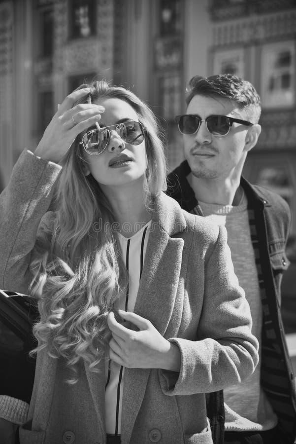 Стильные пары в пребывании солнечных очков на улице стоковые фотографии rf