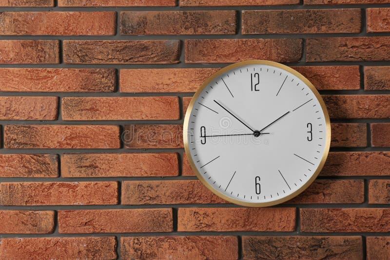Стильные сетноые-аналогов часы вися на кирпичной стене стоковое фото rf
